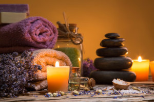 Spa still-life with stacked of stone and burning candles, close-up.
